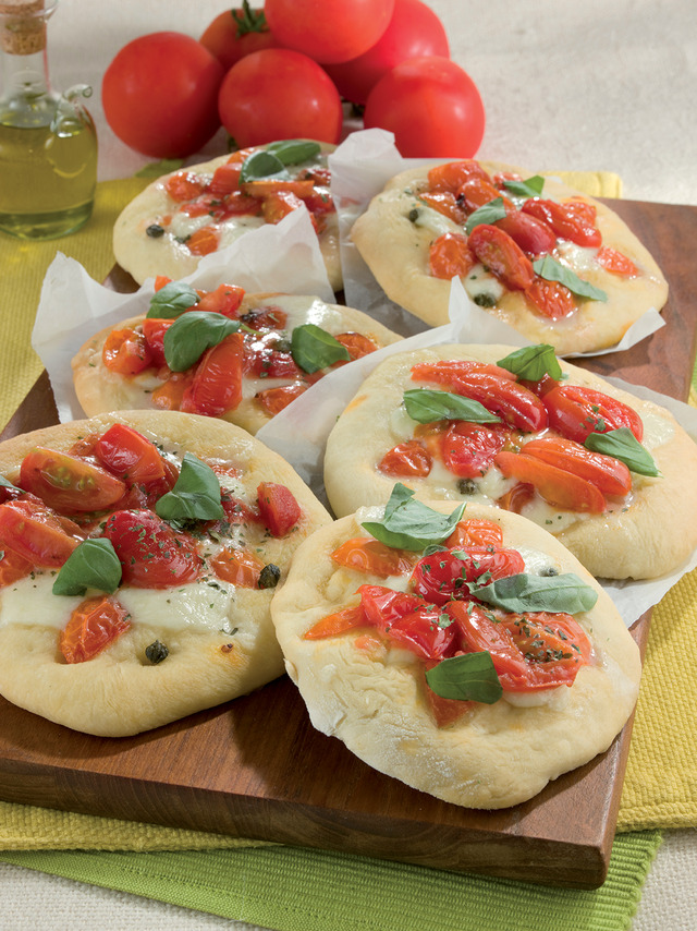 Маленькие пиццы с  кусочками помидор и   базиликом